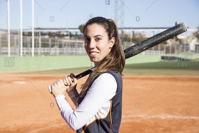 Portrait of smiling female baseball player with a baseball bat