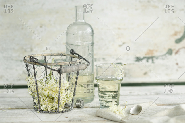 Glass bottle and glass of elderflower syrup and elderflowers in wire basket