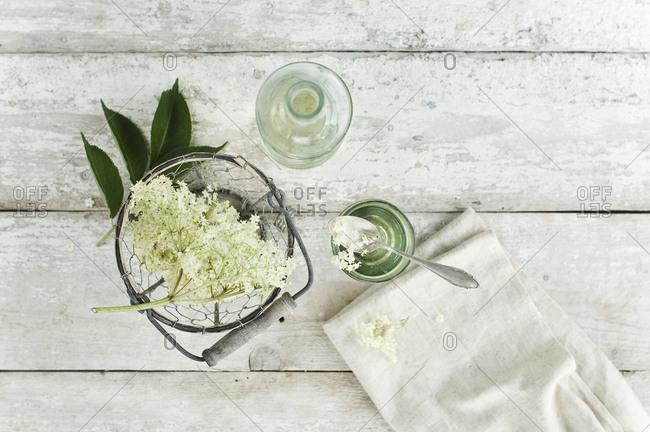 Glass bottle of elderflower syrup- glass with flavored water and elderflowers in wire basket