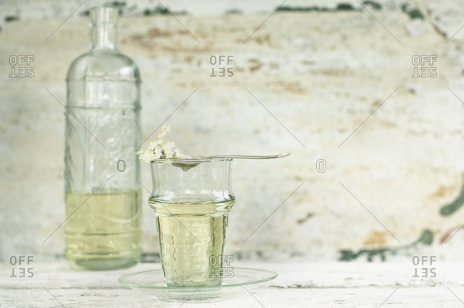 Glass and glass bottle of elderflower syrup