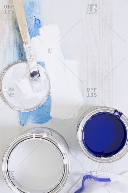 Used paint brush and paint tins with blue and white varnish