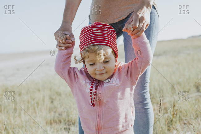 Smiling toddler holding mother's hands on a meadow