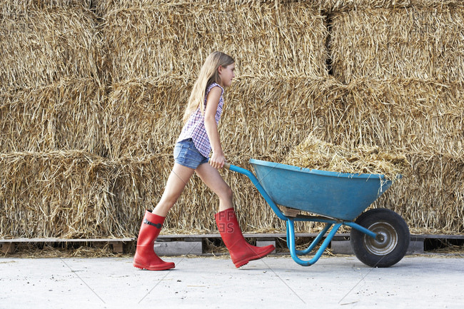 Girl walking with wheelbarrow on horse farm