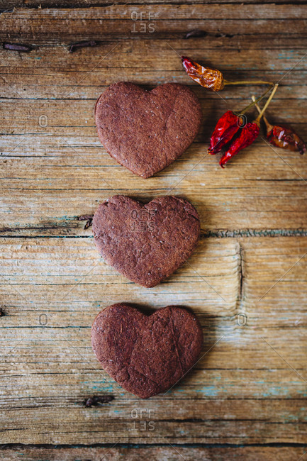 Three heart-shaped chocolate shortbreads and dried chili pods on wood