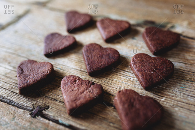 Nine heart-shaped chocolate shortbreads in rows on wood