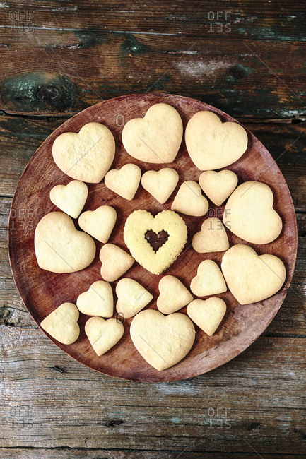 Wooden plate of heart-shaped shortbreads on wood