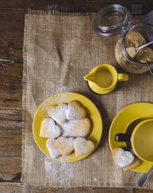 Heart-shaped shortbreads sprinkled with icing sugar on plate- cup of milk and milk pitcher on jute