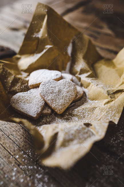 Heart-shaped shortbreads sprinkled with icing sugar on paper