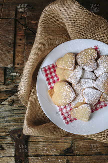 Heart-shaped shortbreads sprinkled with icing sugar on napkin and plate