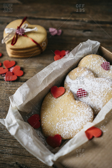 Cardboard box of three heart-shaped shortbreads sprinkled with icing sugar