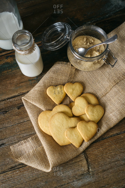 Heart-shaped shortbreads on jute- glass bottle of milk and preserving jar of brown sugar