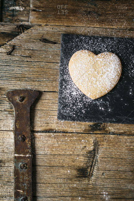 Heart-shaped Shortbread sprinkled with icing sugar on slate and wood