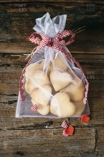 Sachet of heart-shaped shortbreads on wood