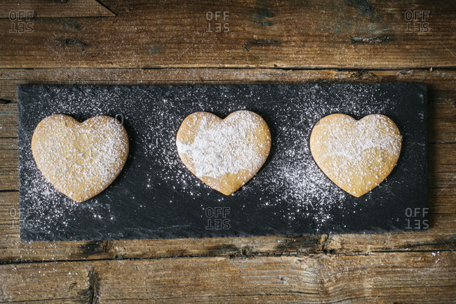 Row of three heart-shaped shortbreads sprinkled with icing sugar on slate and wood