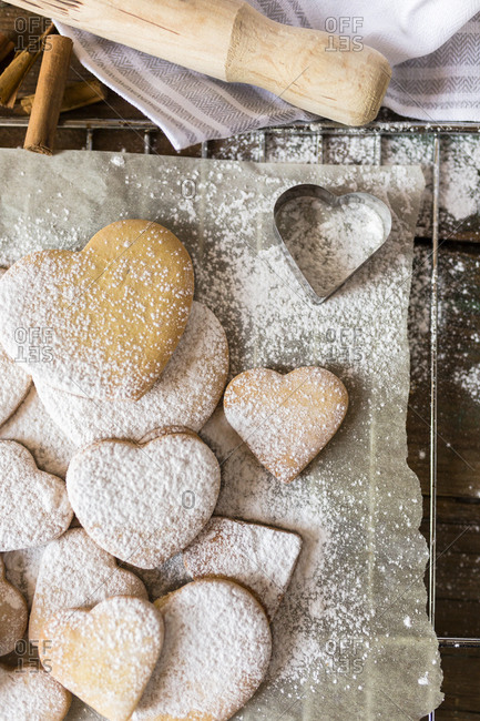 Heart-shaped shortbreads sprinkled with icing sugar and cookie cutter on parchment paper