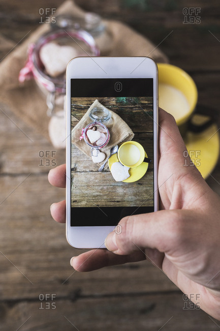 Woman taking a photo of shortbreads and cup of milk with her smartphone- close-up