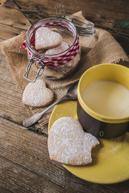Preserving jar of heart-shaped shortbreads sprinkled with icing sugar and cup of milk