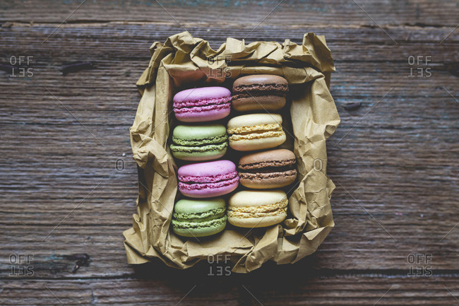 Different macarons in a box on wood
