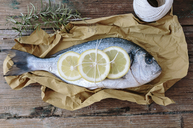 Sea Bream on a baking paper with lemon and rosemary