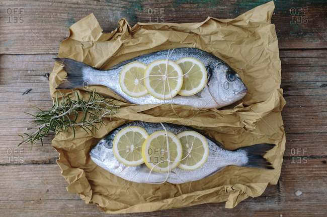 Two Sea Bream on a baking paper with lemon and rosemary