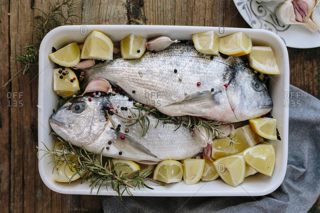 Sea Breams in baking dish with fresh lemon- rosemary and pepper