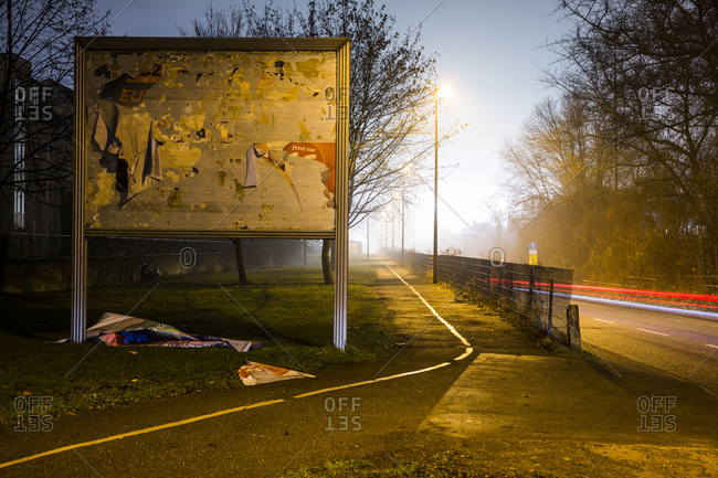 Billboard with destroyed advertising at night