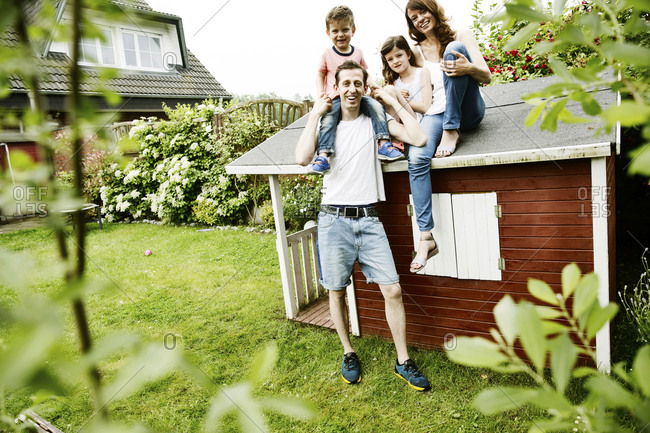 Happy family sitting on roof of their garden shed
