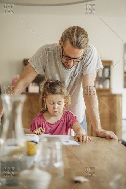 Father checking homework of his daughter
