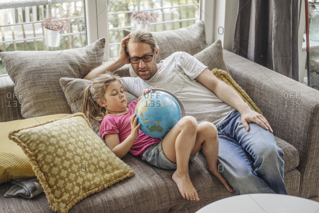 Father and daughter lying with globe on sofa