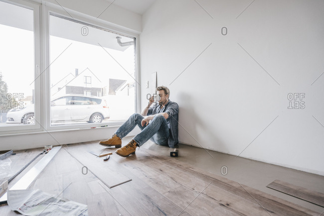 Mature man fitting flooring in new home- drinking coffee and taking a break