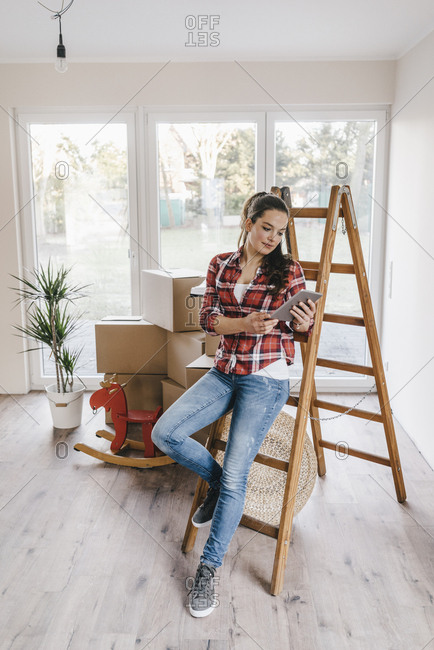 Mature woman moving house- leaning against ladder- using tablet