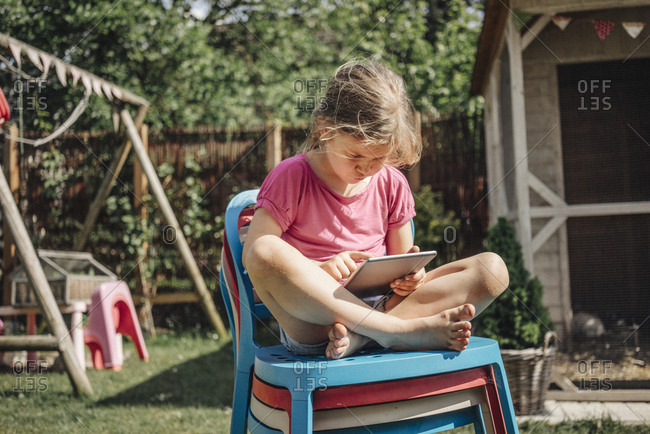 Girl sitting on stack of chairs in garden using tablet