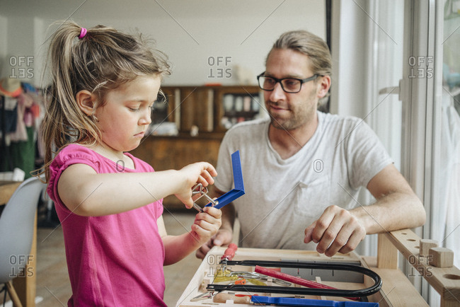Father looking at daughter working with tools