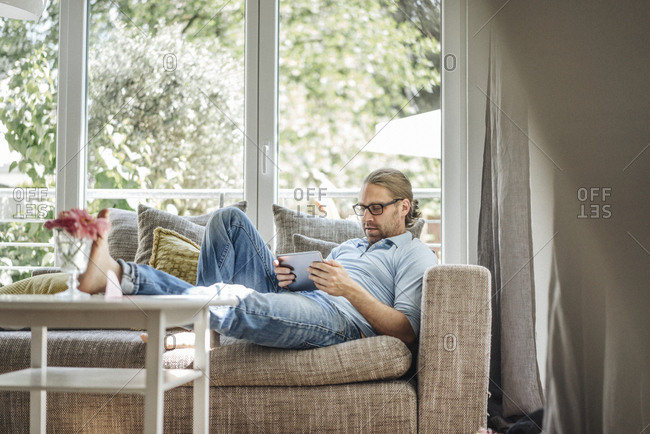 Man relaxing on couch using tablet