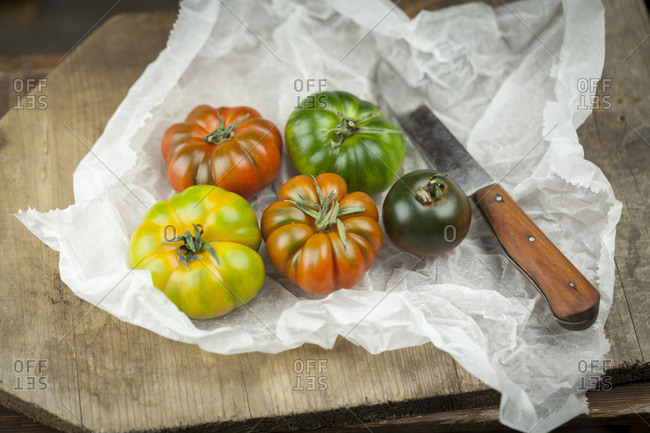 Fife different Oxheart Tomatoes and knife on paper