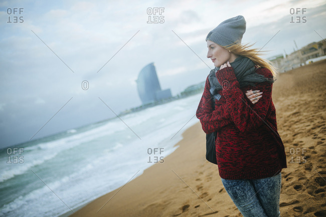 Spain- Barcelona- young woman on the beach in winter