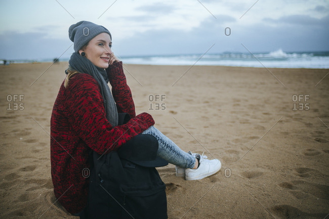 Smiling young woman sitting on the beach in winter