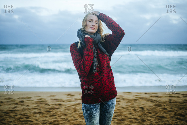 Young woman with eyes closed on the beach in winter