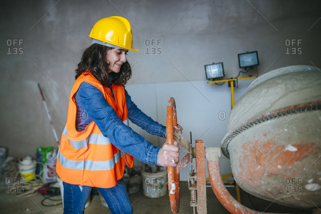 Woman working with a concrete mixer on construction site