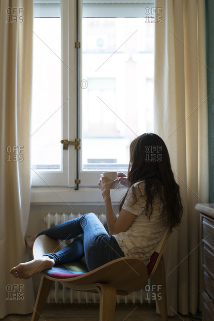 Woman with cup of coffee sitting on chair at home looking through window
