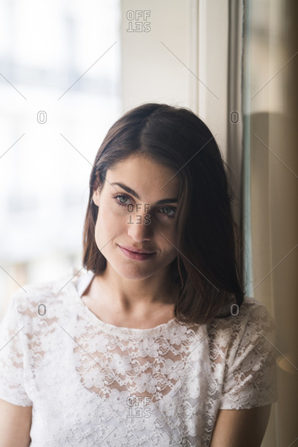 Portrait of content woman in front of window
