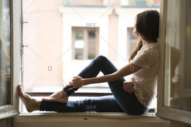 Woman sitting on window sill looking through open window