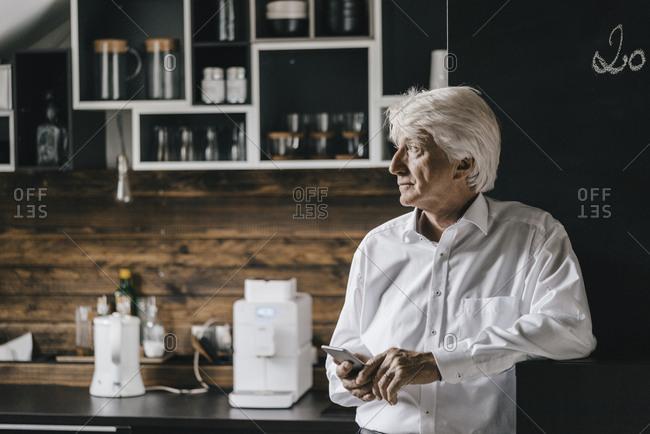 Senior businessman with smartphone in the kitchen