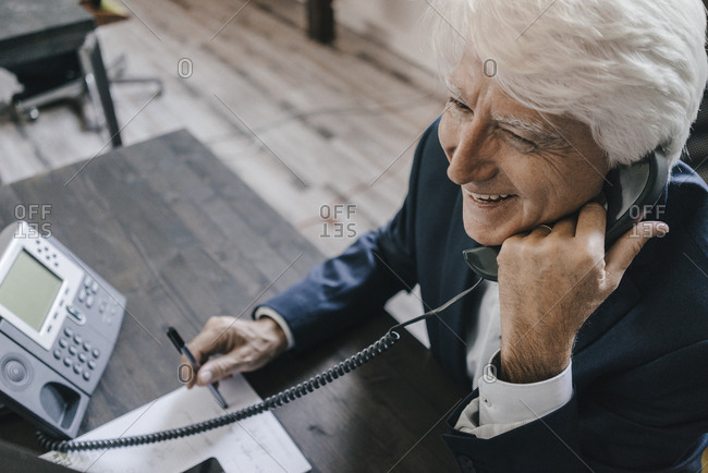 Smiling senior businessman on the phone in his office