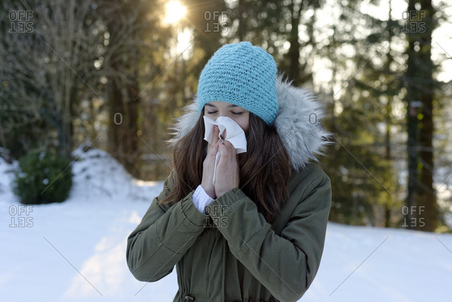 Teenage girl wearing woolly hat blowing her nose in winter