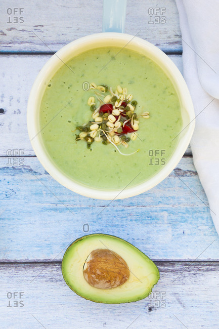 Saucepan of avocado cucumber soup garnished with sprouts