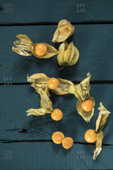 Whole and sliced physalis on colored wood