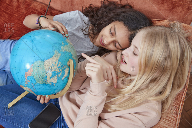 Two girls lying on couch pointing at globe