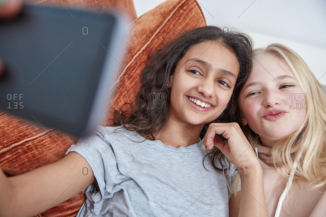 Two happy girls on couch taking a selfie