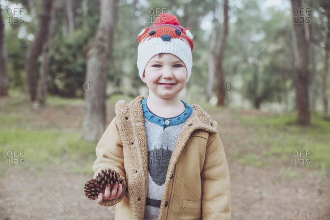 Portrait of boy wearing wooly hat holding pine cones in forest